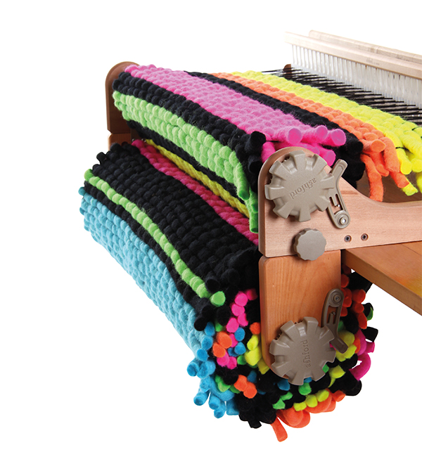 product image from Ahsford's website showing the freedom roller attached below the front of a rigid heddle loom. There is weaving in progress, it is a bright multicoloured rug woven with very thick springy-looking weft.